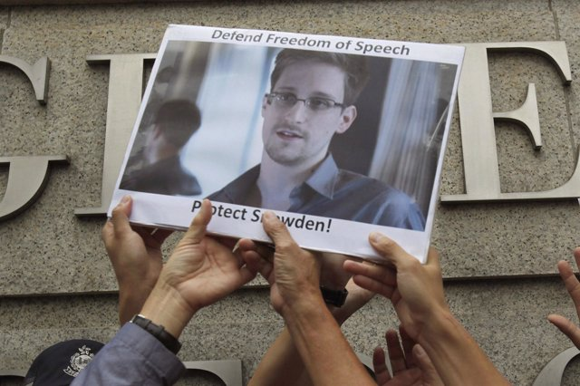 Manifestantes con una foto de Edward Snowden
