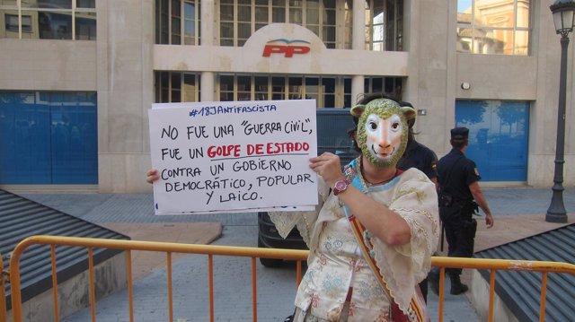 Una manifestante frente a la sede del PP valenciano