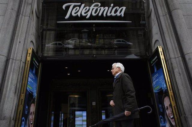 Un hombre camina frente a un edificio de Telefónica en el centro de Madrid. Foto