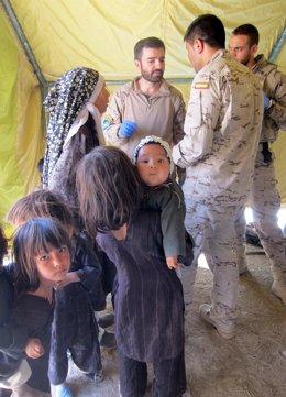 Un traductor ayuda a un militar español a prestar asistencia en Afganistán
