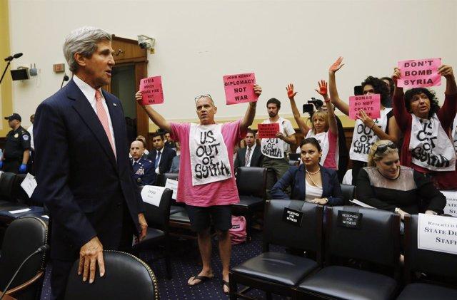 El secretario de Estado de Estados Unidos, John Kerry, pasa junto a manifestante