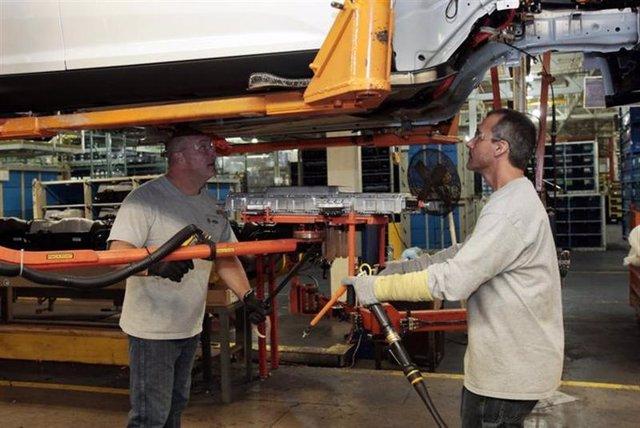 Trabajadores de una planta de Ford instalan un cargador de baterías