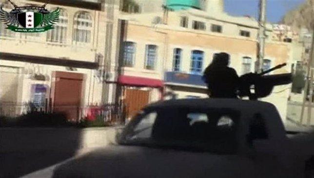 Un vehículo rebelde sirio con una ametralladora de alto calibre maneja en Maalou
