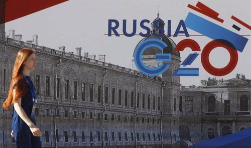 Una empleada pasa junto a un símbolo de la cumbre G-20 en Strelna cerca St. Pete