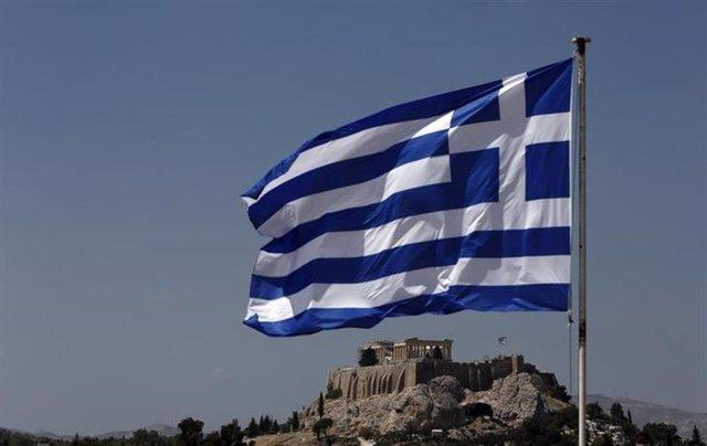 Una bandera de Grecia ondea frente a la Acrópolis en Atenas. Agosto 21, 2013. RE