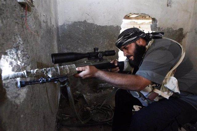 Un combatiente del rebelde Ejército de Siria Libre apunta su arma sobre un aguje