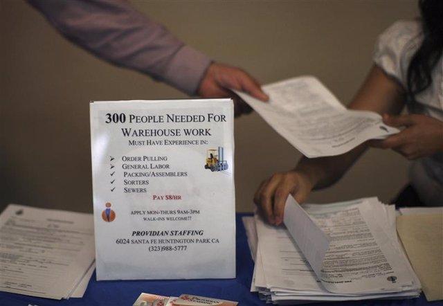 Unos representantes de la firma Providian Staffing entregan aplicaciones de empl