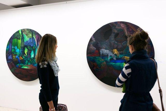 Dos estudiantes observan uno de los cuadros