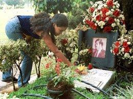 Una mujer pone flores en la tumba de Pablo Escobar