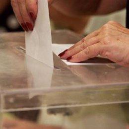 Una persona introduciendo un voto