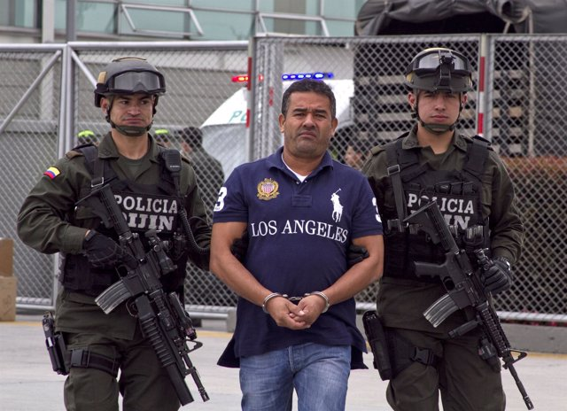 Colombian alleged drug trafficker Diego Perez Henao is escorted by policemen bef