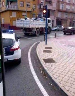 Un camión escoltado por la Policía Local recoge la basura en Alicante
