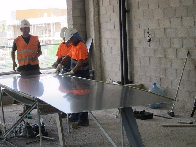 Trabajadores de la construcción en una obra con casco