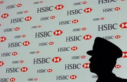 A security guard stands in front of a screen at an HSBC news conference in Hong