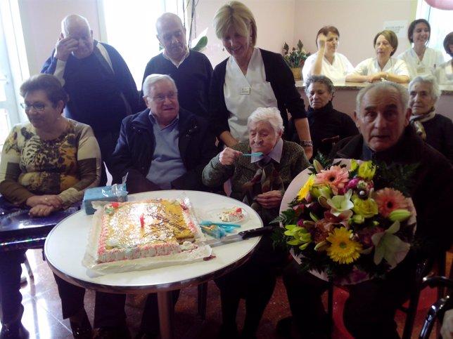 Josefa Alvárez prueba su tarta rodeada de familiares y trabajadores del centro