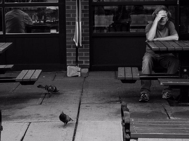 Hombre solo sentado en una mesa en la calle con dolor de cabeza