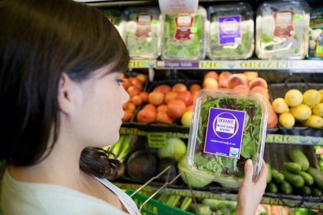 Mujer en el supermercado comprando verduras orgánicas