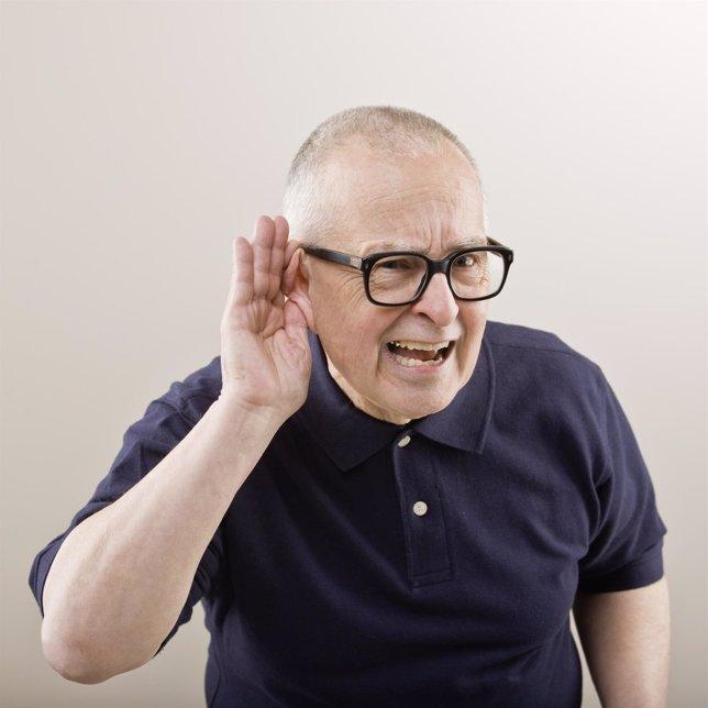 Hombre mayor tratando de escuchar con la mano en el oído