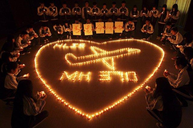 Malasia enciende velas para pedir por los pasajeros del avión desaparecido