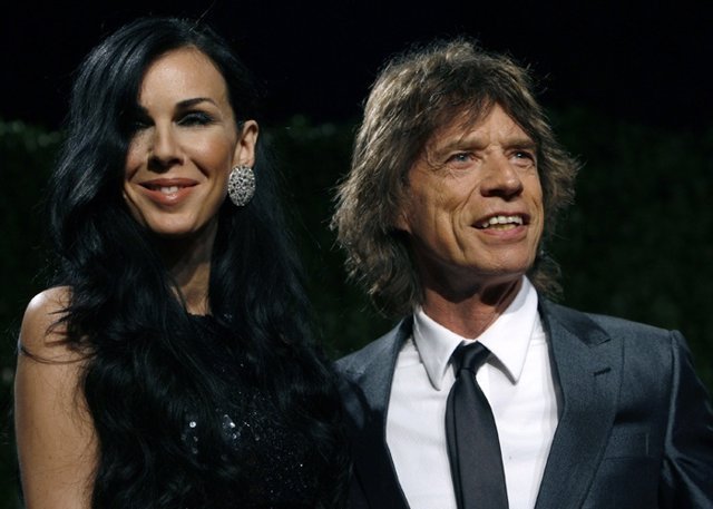 Designer L'Wren Scott and rock musician Mick Jagger pose as they arrive at the 2