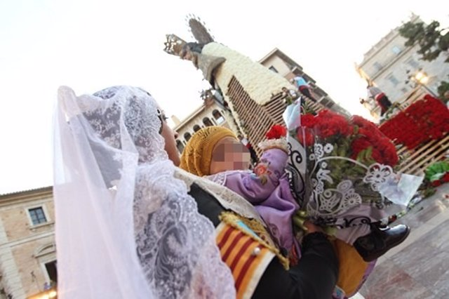 Una fallera y un bebé pasan ante la imagen de al Virgen en la Ofrenda
