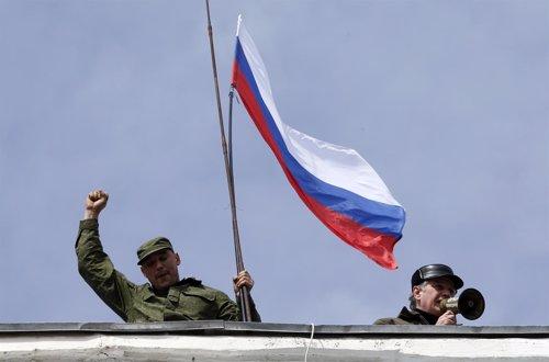 Soldados prorrusos agitan una bandera Rusa en un cuartel en Crimea
