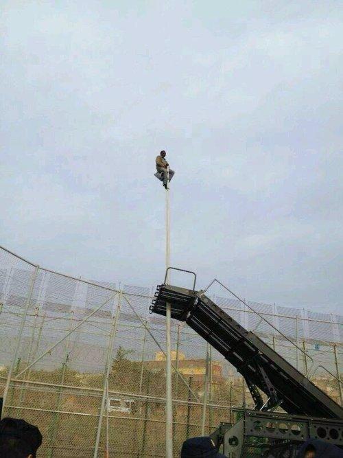 Inmigrante subido a una farola en la valla de Melilla