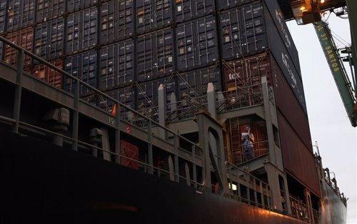 Un trabajador portuario junto a una serie de contenedores