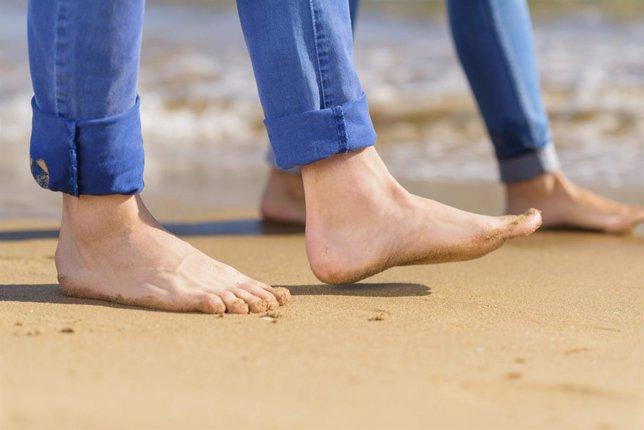 Pareja con los pies descalzos paseando por la playa