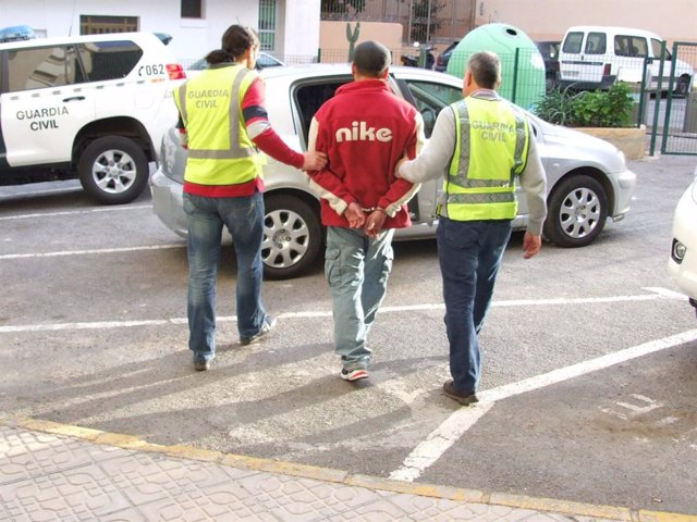 Dos agentes trasladan a uno de los detenidos al coche policial