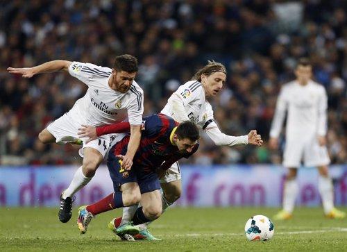 Xabi Alonso y Modric pelean un balón con Leo Messi
