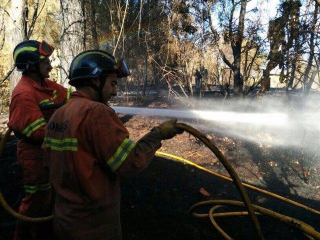 Bomberos refrescando la zona del incendio