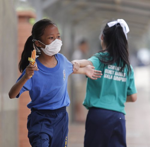 A student wearing a face mask plays with her friend outside their school in haze