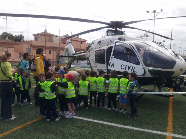 Niños junto a un helicóptero de la Guardia Civil