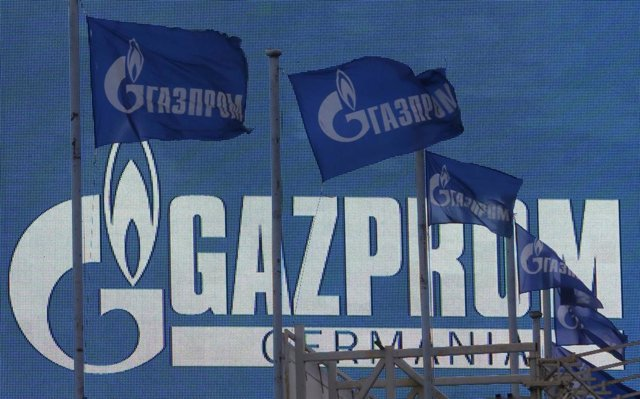 Flags fly near na advertising screen displaying the logo of Gazprom company, in
