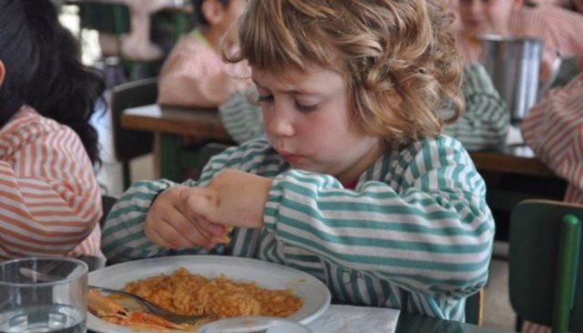 Niño comiendo en una escuela catalana, beca comedor