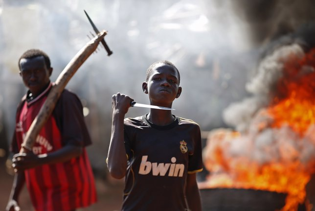 A boy gestures in front of a barricade on fire during a protest after French tro
