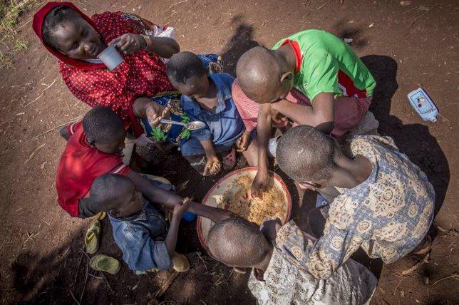 Seis de los hijos comen de un bol en el campamento