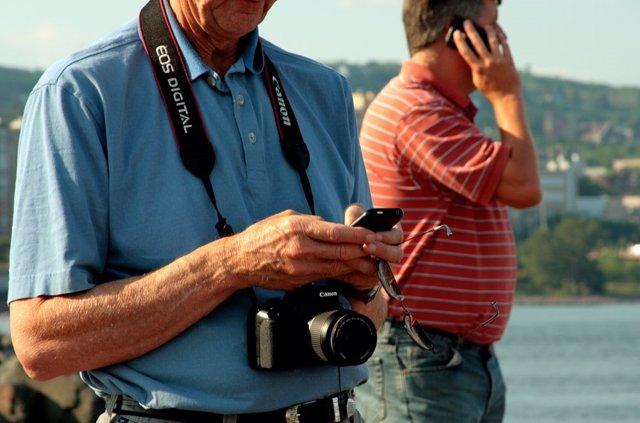 Turista en la playa con cámara y teléfono móvil smartphone verano vacaciones