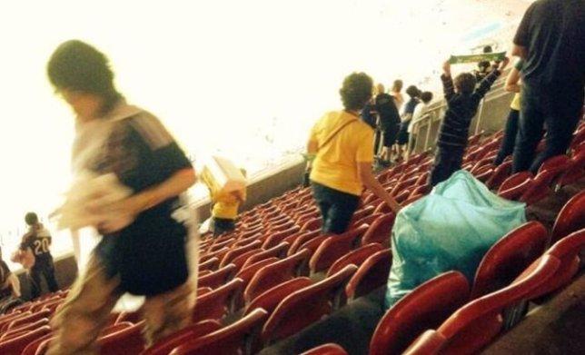 Aficionados japoneses limpiando el estadio