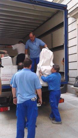 Operarios descargan muebles para la proclamación