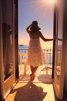 Mujer en habitación con vistas al mar