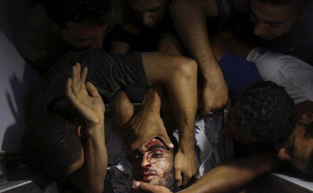 Personas se acercan al cuerpo de un militante palestino en Gaza