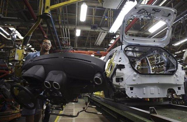 Un trabajador brasileño ensambla un vehículo en una planta de la automotriz Ford