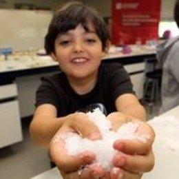 Un niño con nieve artificial creada en el taller