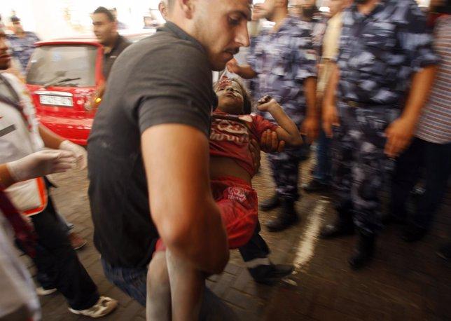 Un hombre lleva a su hija herida tras uno de los bombardeos de Israel