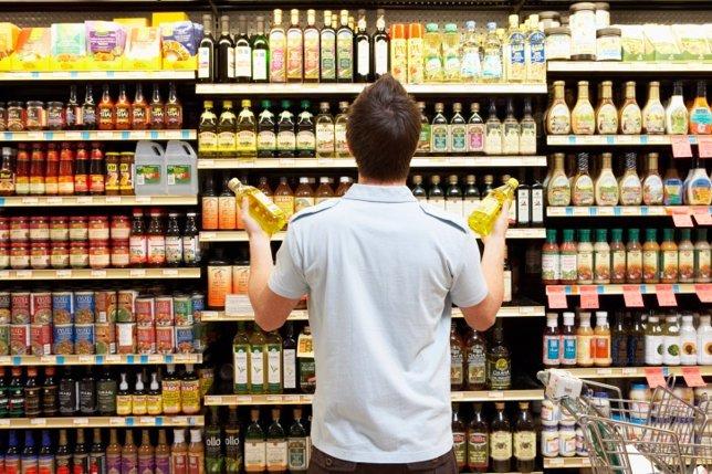Un hombre comprando en un supermercado mirando los aditivos