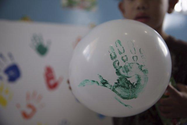 Un niño juego con un globo que lleva su mano pintada