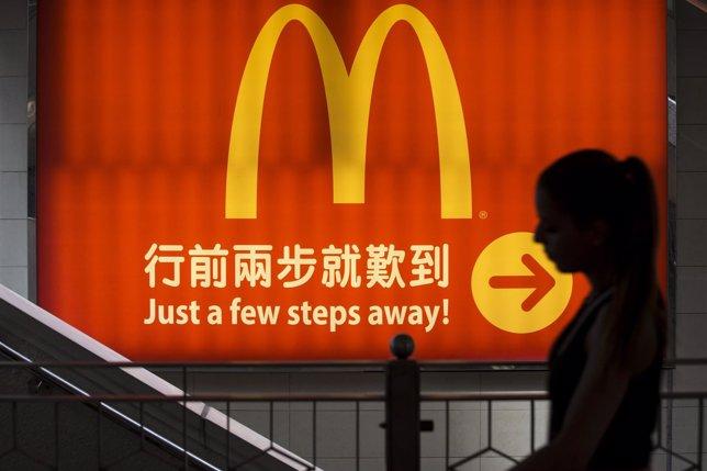 Una mujer pasa frente a un logo de McDonald's en Hong Kong