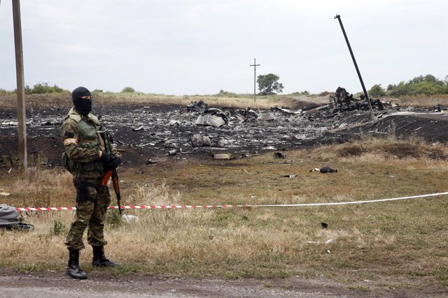 Pro-Russian separatist stands near a body at the crash site of Malaysia Airlines